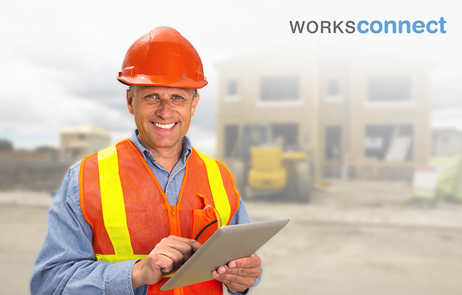 A royalty free image from the construction industry of a building contractor using a tablet computer at a new housing development.